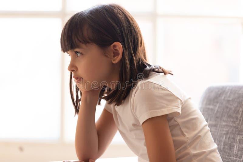 侧视图学龄前可爱的女孩在家坐长沙发 库存图片