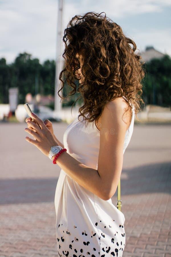侧视图年轻女人佩带的白色礼服 库存照片