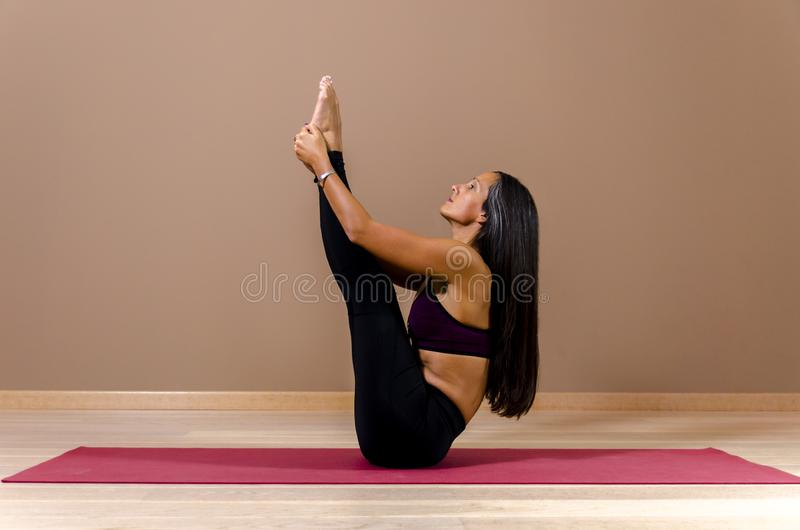 侧视图有吸引力年轻在瑜伽姿势 免版税库存照片