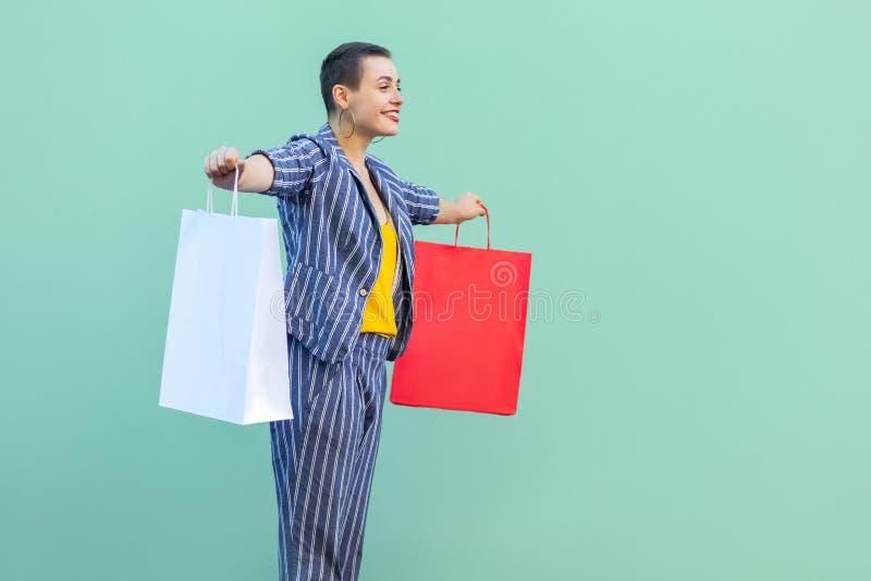 侧视图满意与镶边衣服身分的短发年轻女人,拿着有被举的胳膊的购物带来,暴牙的微笑 免版税库存照片