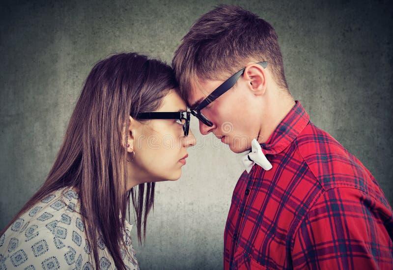 侧视图男人和妇女势均力敌看与仇恨彼此 库存图片