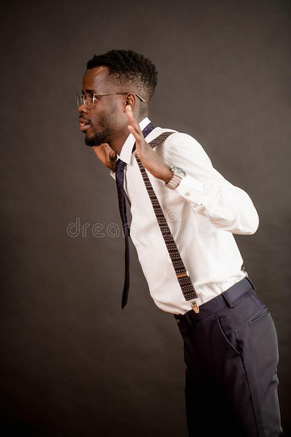 侧视图短在正式衣物的年轻非洲的人跳舞在企业党 免版税库存图片