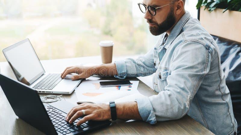 侧视图 行家有胡子的商人在咖啡馆坐,研究两台膝上型计算机 遥远自由职业者工作 在线教育 免版税库存照片