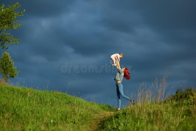 侧视图og年轻母亲在手上的拿着小女儿在夏天领域 免版税库存照片