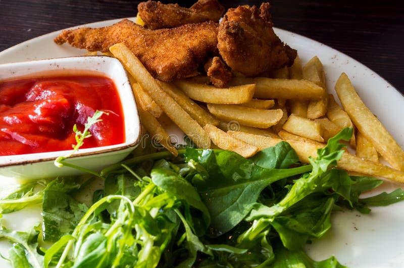 便当产品:薯条和鸡块在木桌,西红柿酱,绿色上 库存照片