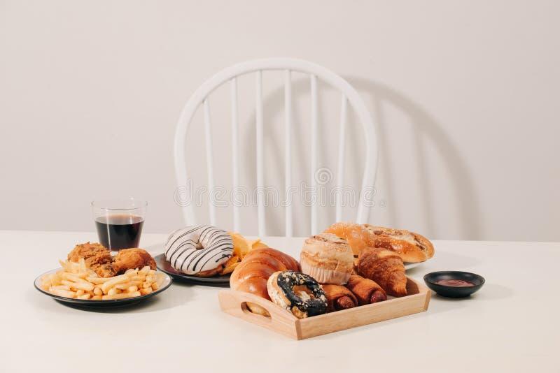 便当和不健康的吃概念-关闭汉堡包或乳酪汉堡,油炸乌贼圆环,薯条,饮料和 免版税库存照片