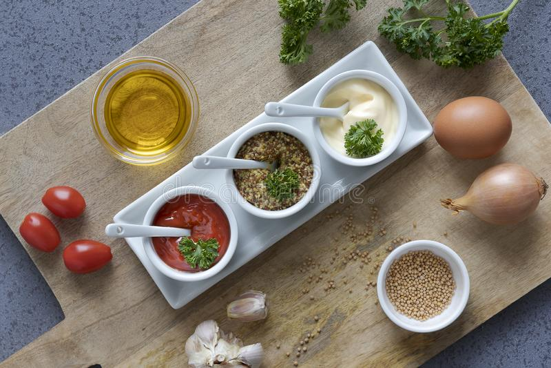 便当调味番茄酱、芥末和蛋黄酱在碗在木切板 免版税库存图片