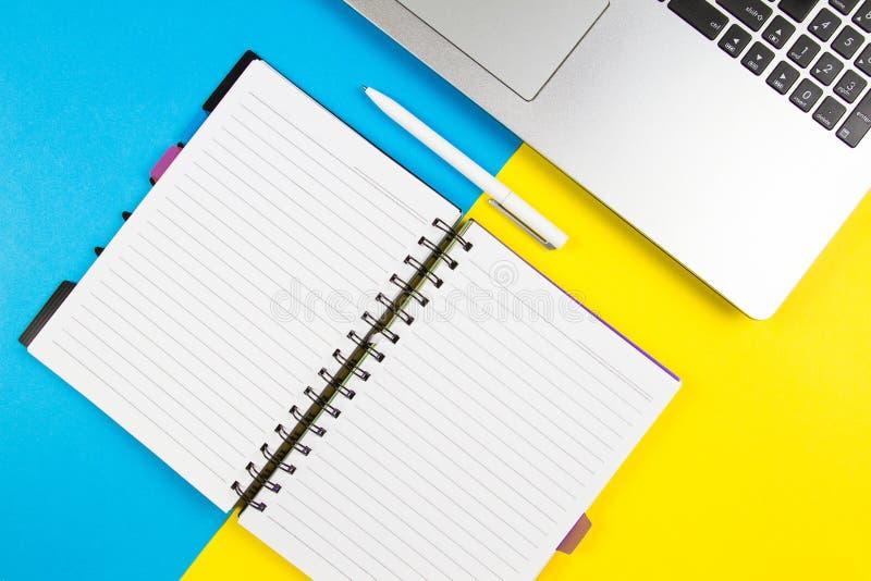 便携式计算机、开放纸笔记本和白色笔在蓝色和黄色颜色背景 顶视图,文本的拷贝空间 库存图片