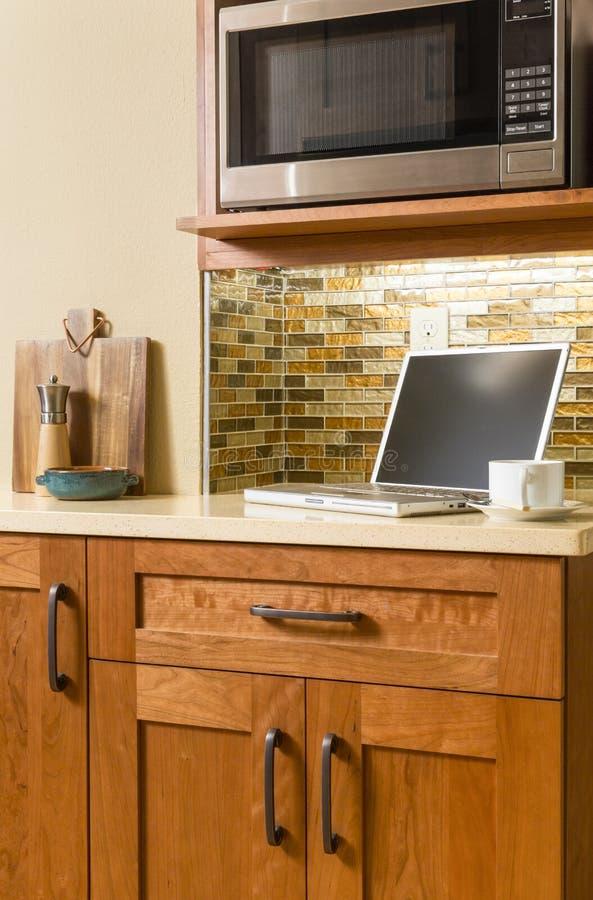 便携式计算机和咖啡杯在柜台在当代家庭厨房里有木内阁和玻璃瓦片backsplash的 免版税库存照片