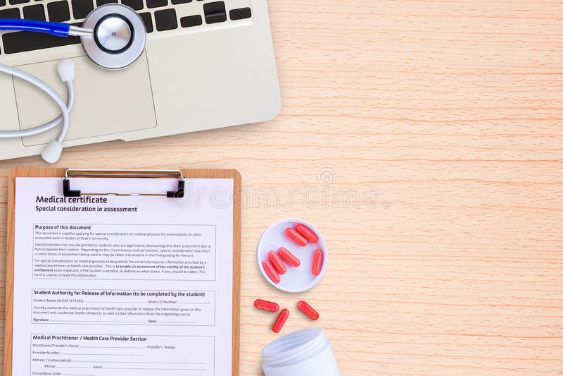 便携式计算机和药片与蓝色听诊器在木书桌上 库存图片