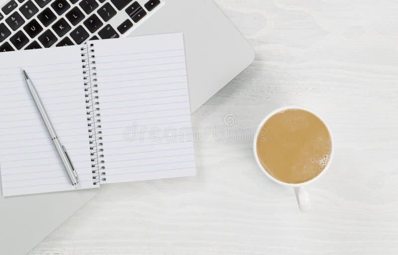 便携式计算机用咖啡和空白的笔记薄在白色桌面上 免版税库存图片