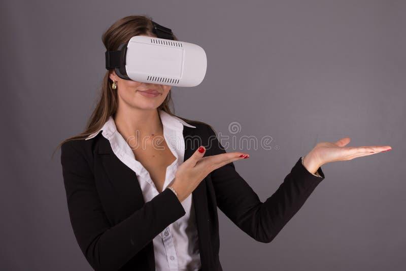 便携的技术VR玻璃的女商人 一套西装的确信的少妇在虚拟现实耳机 免版税库存照片