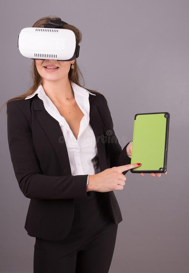 便携的技术VR玻璃的女商人 一套西装的确信的少妇在虚拟现实耳机 图库摄影