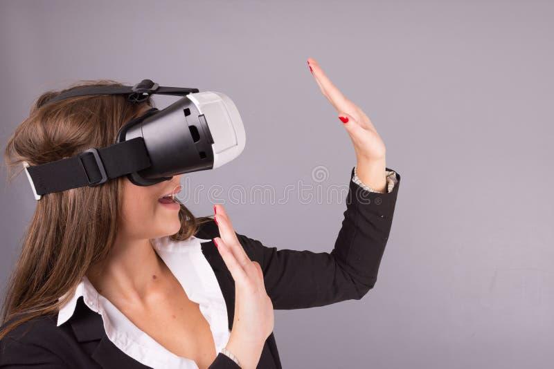 便携的技术VR玻璃的女商人 一套西装的确信的少妇在虚拟现实耳机 库存图片
