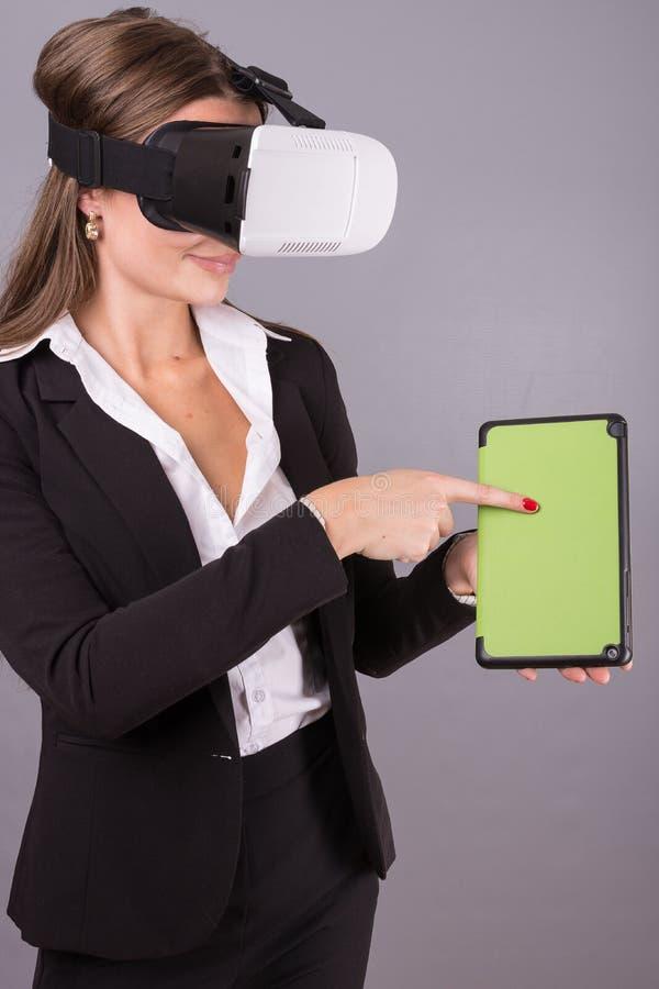 便携的技术VR玻璃的女商人 一套西装的确信的少妇在虚拟现实耳机 免版税库存图片