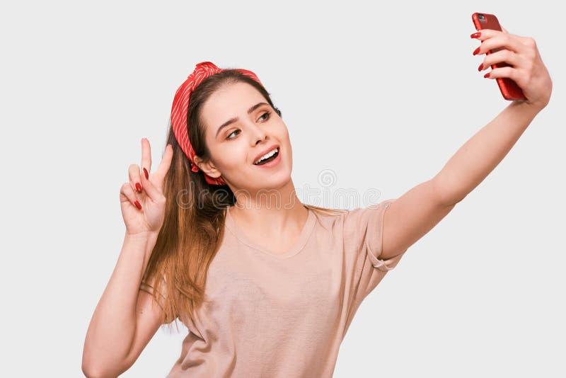 便服和红色头饰带的美丽的年轻欧洲妇女,采取在白色演播室墙壁的自画象 免版税库存照片