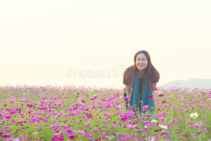 便服微笑和身分的愉快的亚裔女孩在波斯菊在葡萄酒图片样式的花田 免版税库存图片