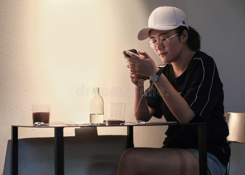 便服的一个亚裔夫人检查她的电话 库存图片