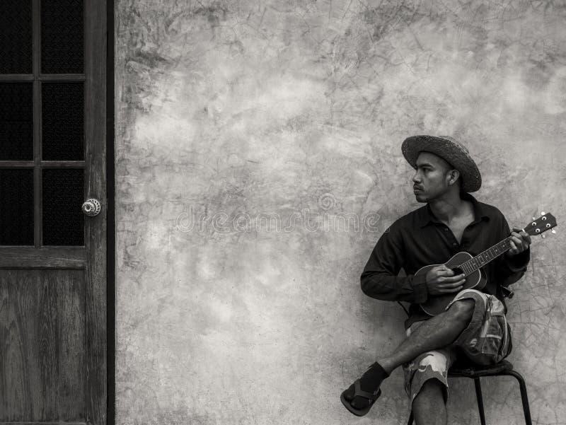 便服的亚裔音乐家人坐椅子和使用 免版税库存照片