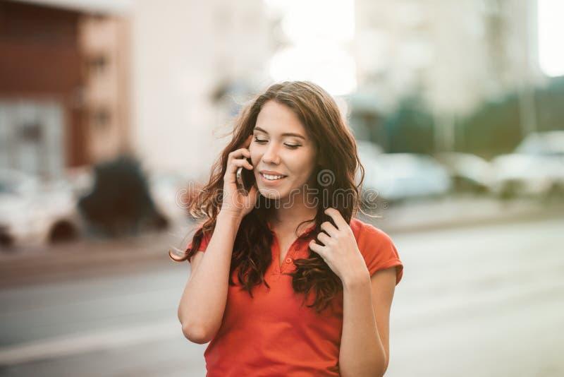 便服的俏丽的女孩在一个手机谈话,当走在日落时光时的城市街道 免版税库存照片