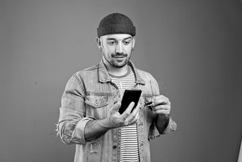 便服的惊奇与在他的智能手机的消息的正面人画象  图库摄影