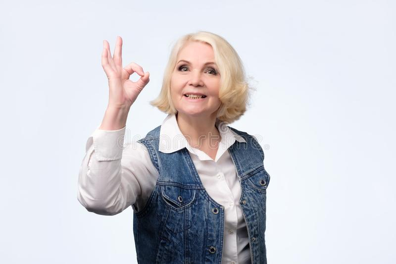 便服的白肤金发的资深妇女显示好标志 库存图片