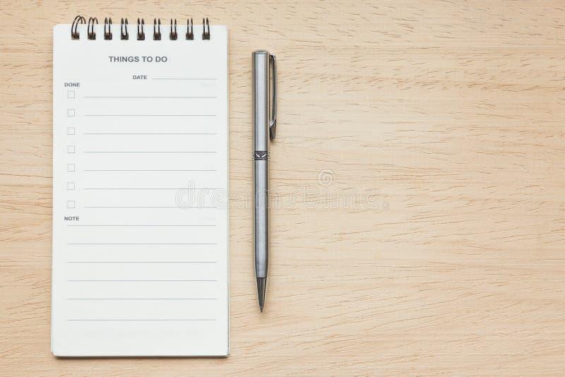 便条纸和笔在木纹理背景 免版税库存照片