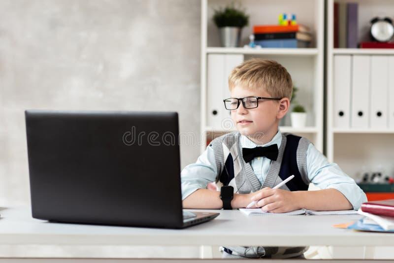 便衣和玻璃的白肤金发的男孩在书桌和看膝上型计算机后坐 免版税库存照片