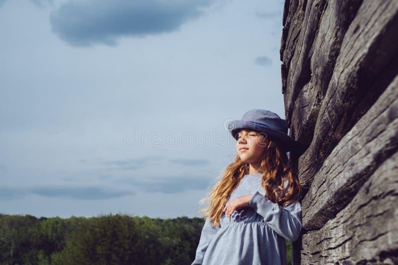 便衣和蓝色帽子的青少年的女孩作倾斜在木墙壁 有效的生活方式 青年时尚 免版税库存图片
