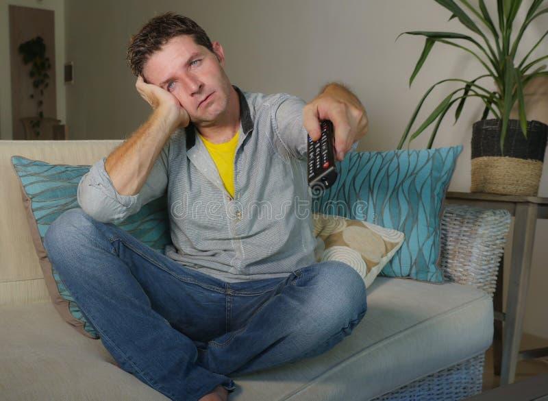 便衣在家乏味的和被挫败的观看的电视电影的年轻可爱的不快乐的人在客厅举行关于的沙发长沙发 免版税库存照片