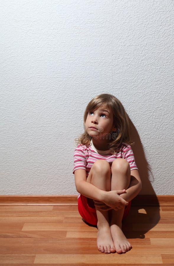 便衣壁角女孩一点看起来哀伤 免版税库存图片