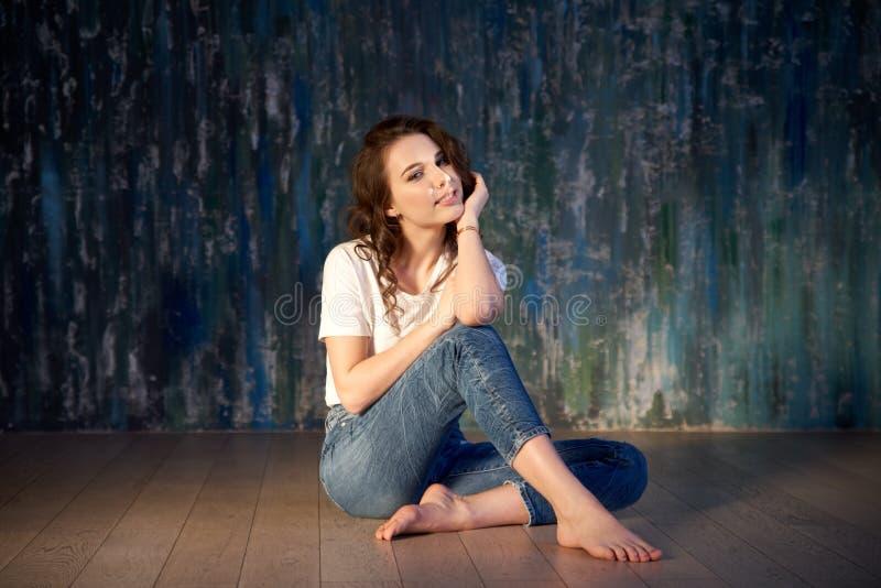 便衣女孩的可爱的年轻深色的妇女坐与快乐的典雅的表情的木地板 免版税图库摄影
