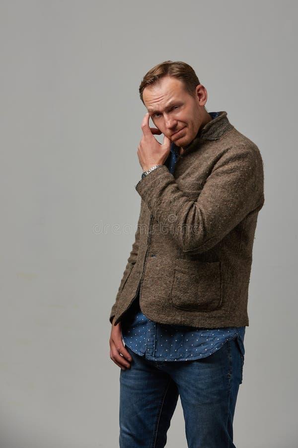便衣的一个人掩藏他的面孔用他的在灰色背景的手 情感,勇敢的面孔 : 图库摄影