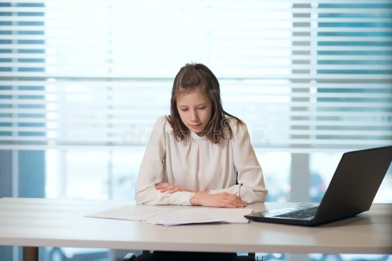 便衣的女孩女实业家,坐在桌上仔细地看文件,运作在计算机 免版税库存照片