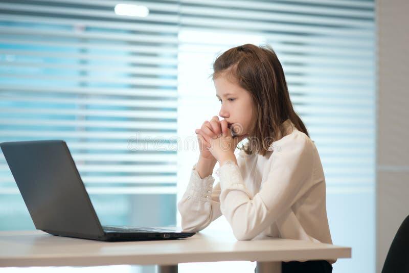 便衣的女孩女实业家,坐在桌上仔细地看文件,运作在计算机 库存图片