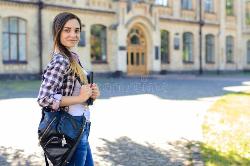 便衣的年轻俏丽的微笑的女学生有backp的 免版税库存照片