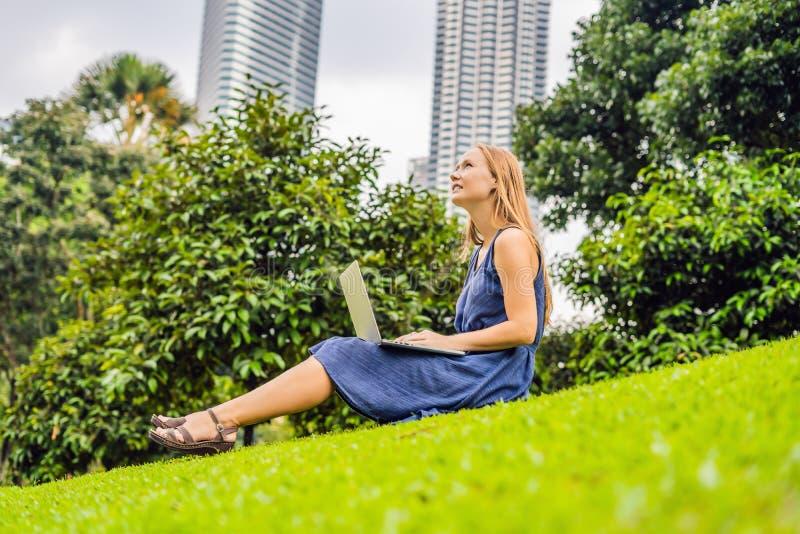 便衣的年轻聪明的学生女性 妇女坐草地面,研究膝上型计算机个人计算机计算机在城市公园 免版税库存照片