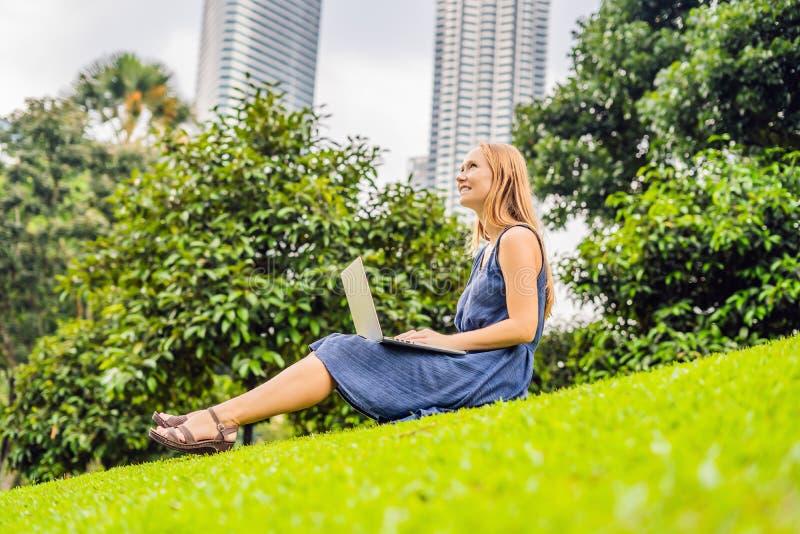 便衣的年轻聪明的学生女性 妇女坐草地面,研究膝上型计算机个人计算机计算机在城市公园 免版税图库摄影