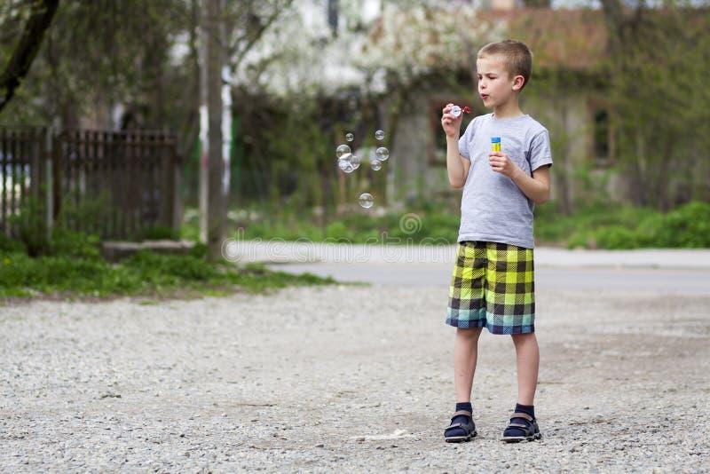便衣的年轻英俊的白肤金发的男小学生有滑稽的ser的 库存照片