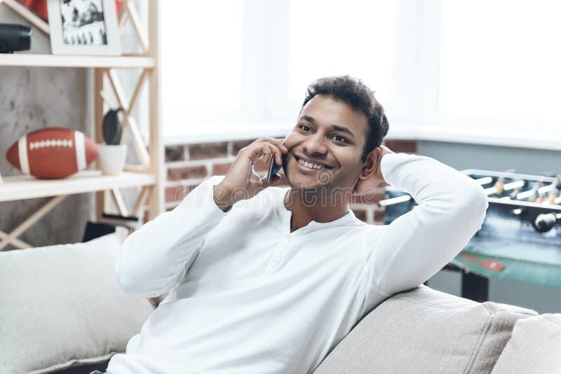 便衣的微笑的人使用手机 免版税图库摄影