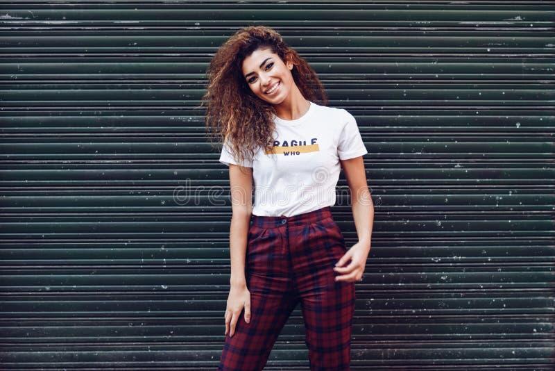 便衣的微笑的阿拉伯女孩在街道 库存照片