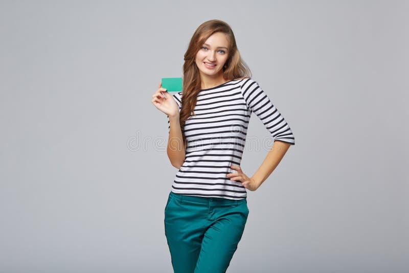便衣的愉快的微笑的女孩,显示无具体金额的信用证卡片 库存照片