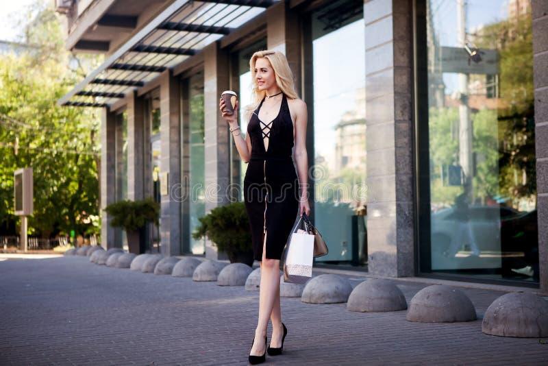 便衣的美丽的性感的白肤金发的女孩有完善的图的走在城市附近的 时尚和城市样式 妇女保留coff 图库摄影