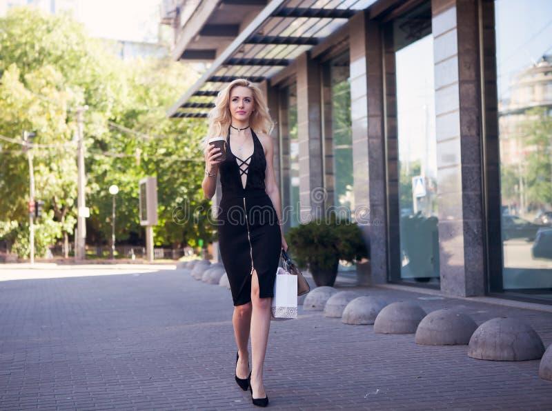 便衣的美丽的性感的白肤金发的女孩有完善的图的走在城市附近的 时尚和城市样式 黑色时髦 免版税库存图片