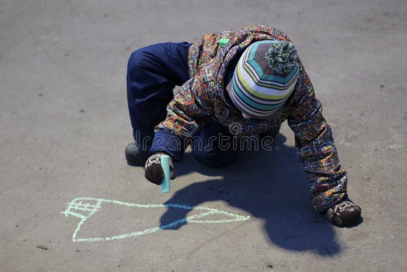 便装和帽子的三岁的男孩画与在路面的白垩在早期的春天 免版税库存照片