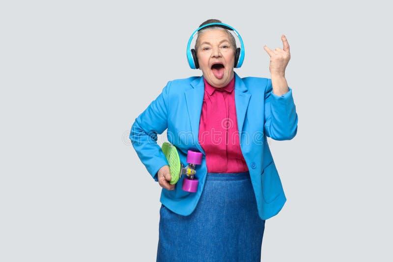 便装样式的时髦滑稽的祖母与蓝色耳机ho 免版税图库摄影