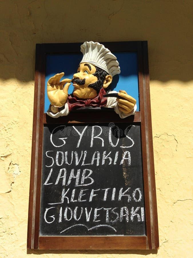 促进希腊烹调的一个室外餐馆标志在雅典,希腊 免版税库存照片