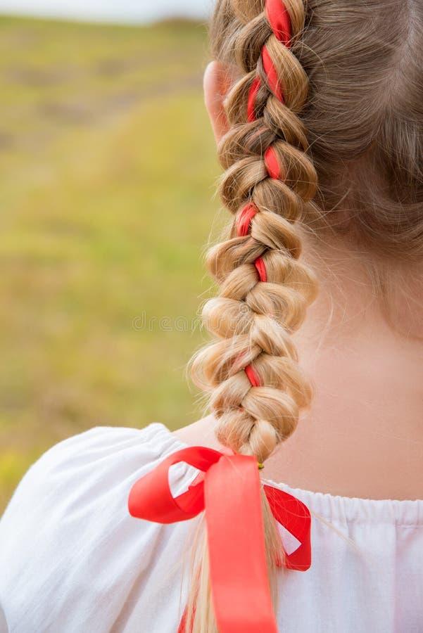 俄国与辫子的女孩斯拉夫的出现与在领域的红色丝带在秋天 免版税库存图片