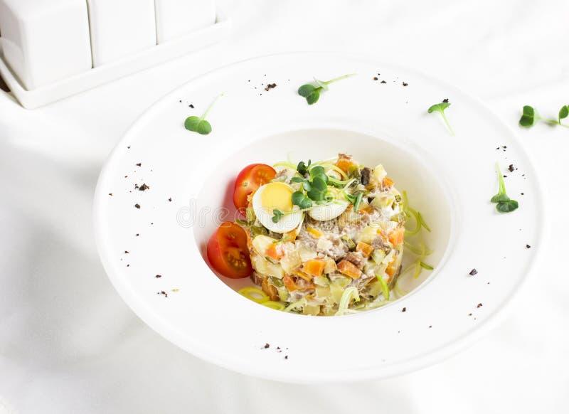 俄国人奥利维尔沙拉用肉、鹌鹑蛋和西红柿 免版税库存照片