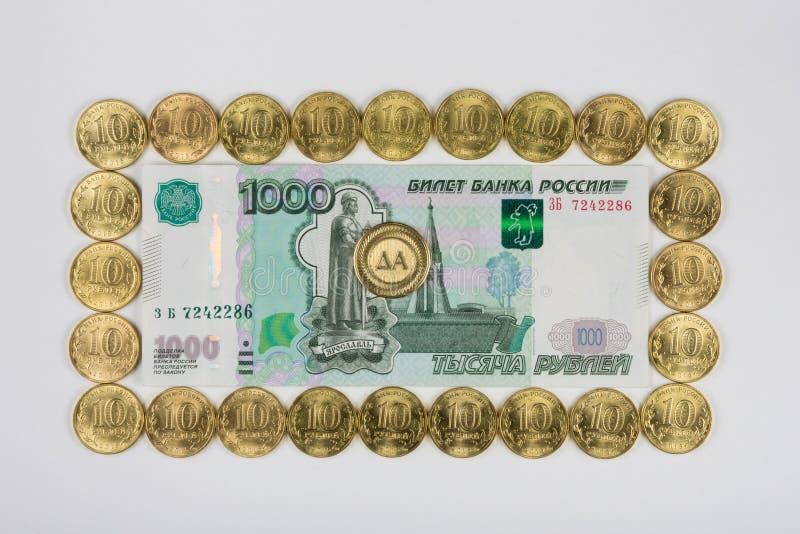 俄国人第一千个张钞票被排行的周长在硬币中间的十枚硬币是a 免版税库存图片